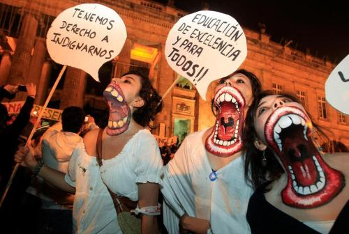 "hangonsloopyhangon:  University students with their necks painted protest at Bolivar square in Bogota, Colombia, Thursday Nov. 3, 2011. Their signs read in Spanish ""We have the right to be outraged,"" left, and ""Excellent education and for all!!"" Students are protesting education reforms planned by the government that propose private funding for public institutions. (Fernando Vergara)"