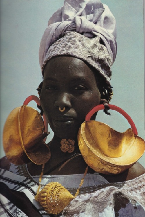 August, 1975- Earmarks of wealth among the Fulanis, giant gold ornaments festoon a woman at Dialloube; a head strap often helps support the heavy earrings. As a family's fortunes increase, more gold may be hammered onto the jewelry. Gleaming filigree- an art form along the Niger- harks back to an age when West African monarchs cornered the bulk of the continent's known gold supply. One 11th century Ghanaian king reportedly possessed a nugget so large that he tethered his horse to it.