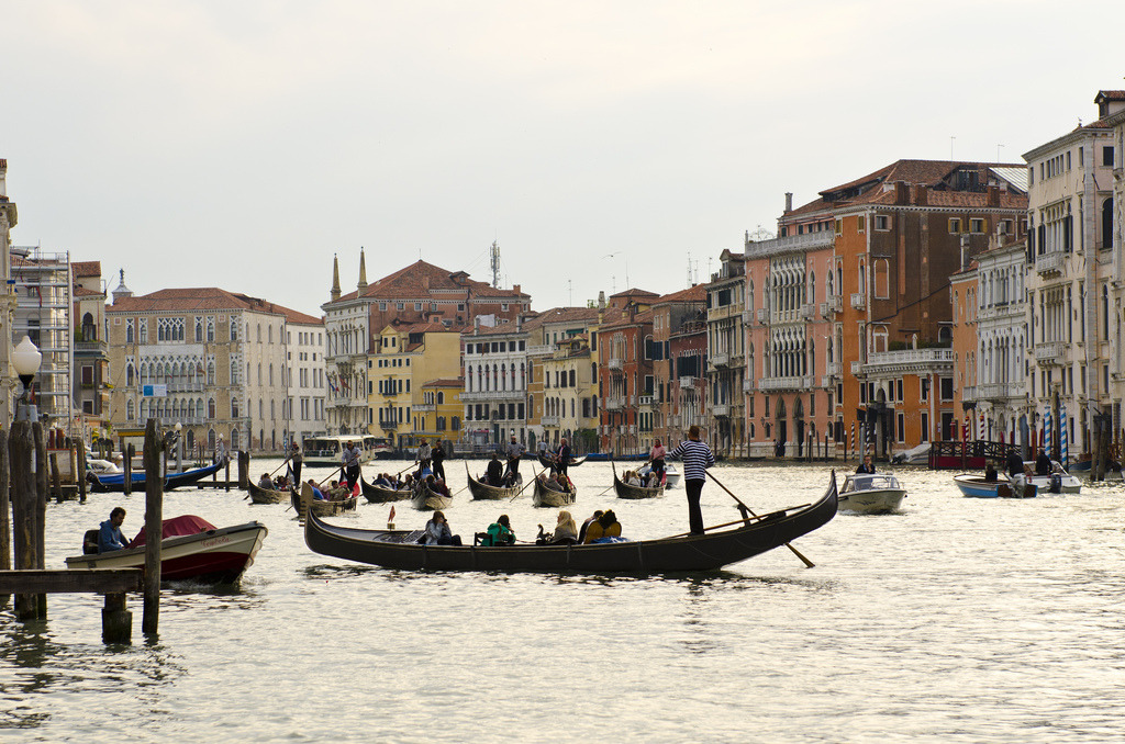 Venise et sa lagune // Venice and its Lagoon A convey of Gondolas seam to race towards branch canal off the Grand Canal in the floating city, Venice. UNESCO française: La ville insulaire fondée au Ve siècle s'étend sur 118 îlots. Elle est  devenue une grande puissance maritime au Xe siècle. Venise dans son  ensemble est un extraordinaire chef-d'œuvre architectural car même le  plus petit monument renferme des œuvres de certains des plus grands  artistes du monde, tels Giorgione, Titien, le Tintoret, Véronèse et  d'autres. UNESCO English: Founded in the 5th century and  spread over 118 small islands, Venice became a major maritime power in  the 10th century. The whole city is an extraordinary architectural  masterpiece in which even the smallest building contains works by some  of the world's greatest artists such as Giorgione, Titian, Tintoretto,  Veronese and others.www.alexanderjebradley.com ©Alexander JE Bradley