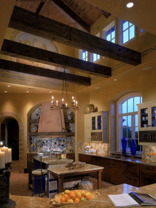 Breathtaking Tuscan style kitchen with a high vaulted ceiling, painted mural wall below the ceiling, exposed beams, and a hint of blue in the tiled stove backsplash and center island