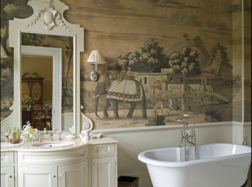 This bathroom gains an exotic touch from a De Gournay antiqued mural wallpaper in a 19th century Romantic style, and a beautiful bow-front vanity with a carved wood mirror