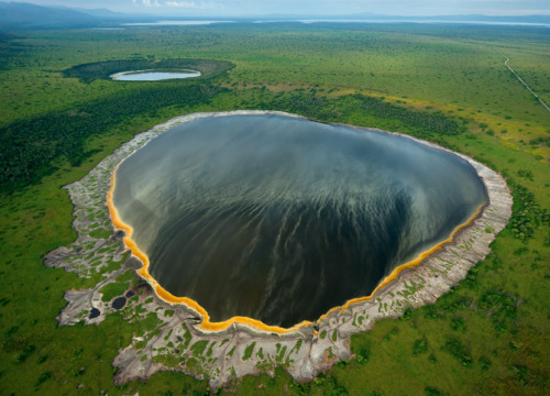 npr:  typicalugandan:  An aerial of the Explosion Craters area in Queen Elizabeth National Park, Uganda. Photography by Joel Sartore  Whoa? Explosion Craters area? Explains All About Uganda:  Explosion craters they are called  because in their hey days eruptions  were so violent that rather than piling  debris around their vents like  some volcanoes, they spewed ash and rock far and  wide. Today, they are  mostly crater (extinct) although some still emit  sulphurous smells.  Click here to learn more about the ones in the picture! —Sarah