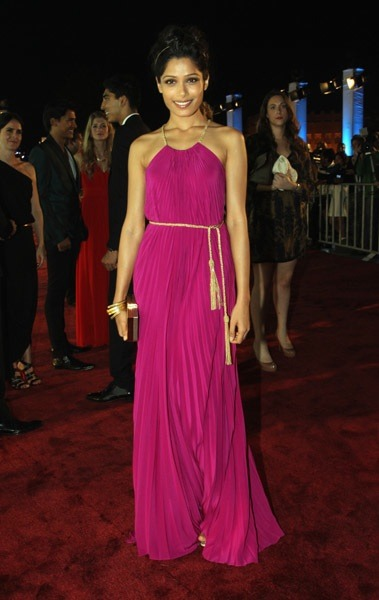 People watching: Actress Freida Pinto looks like a Grecian goddess in a magenta Salvatore Ferragamo gown. Learn more about the full look here »
