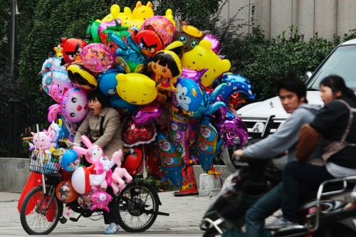 Nanjing, China: A balloon vendor yawns as she waits for customers on her electric bicycle.