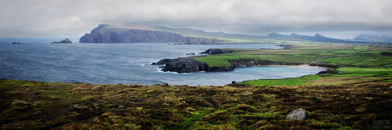 "Clogher Cove by Benjamin Padgett  Sybil Head and the triple peaks known as the Three Sisters appear beyond the cove at An Drum, as viewed from near Clogher Head.  The small white specks on the peninsula are sheep, while the larger specks in the distance are houses. Click here to SEE IT BIG!   This is one of many photos from the ""Dingle, Part II"" post on IRElogue."