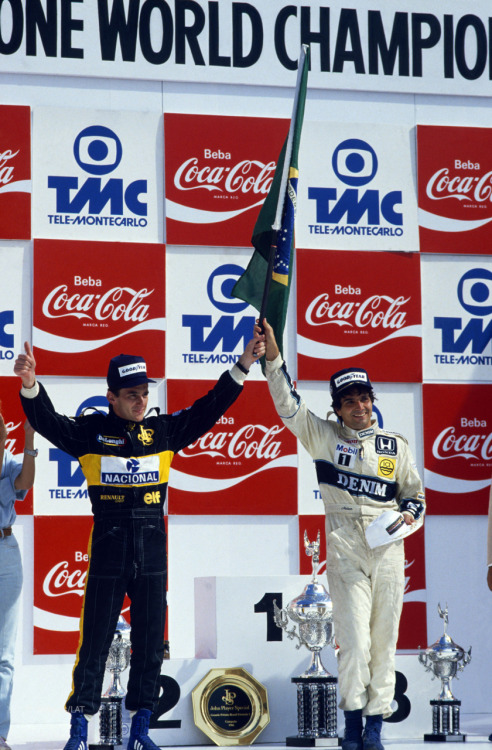 leucocrystal:  Two Brazilians on the podium at their home race: Nelson Piquet (R, 1st) and Ayrton Senna (L, 2nd) raise the bandeira at the Brazilian Grand Prix at Jacarepaguá, 23 March 1986.