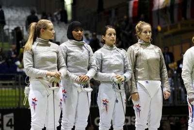 The woman, second from left, is Ibtihaj Muhammad, vying to become the first woman on the US Fencing team to wear a hijab headscarf in the Olympics. You can find the full article here: http://womensmediacenter.com/blog/2011/11/exclusive-in-fencers-hijab%E2%80%94struggle-and-inspiration/