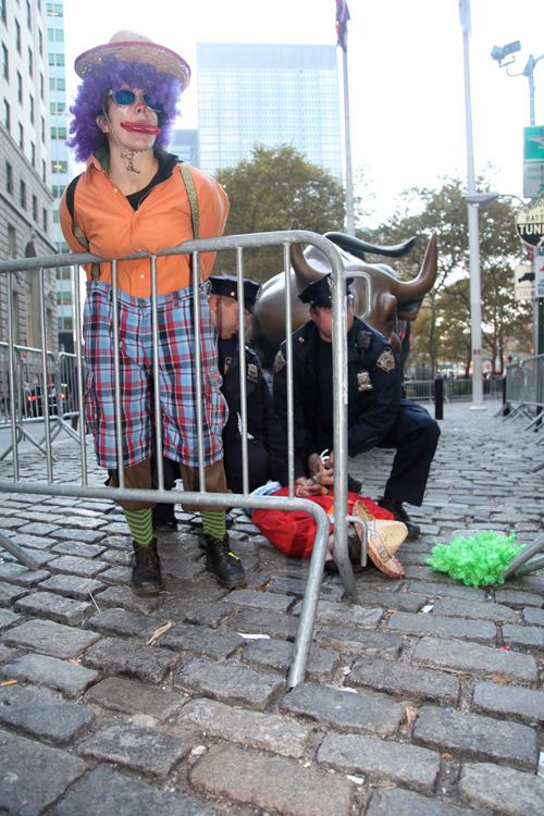 CLOWNS ARRESTED IN NEAR-SUCCESSFUL ATTACK ON WALL STREET BULL - The clowns began spanking and climbing the beast, traditional ways of coaxing a bull into anger in preparation for a Castilian corrida, or bullfight.