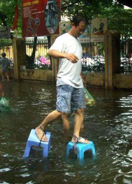 "Flood Proof Plateau Shoes ""Flood platform shoes is not in Thailand, it's Vietnam - probably one of the semi-regular short flash floods that happen in Hanoi.  You can see from the advertising in the background ""Tuyen Sinh"" - ""Seeking students""."" from reader Mattyb"