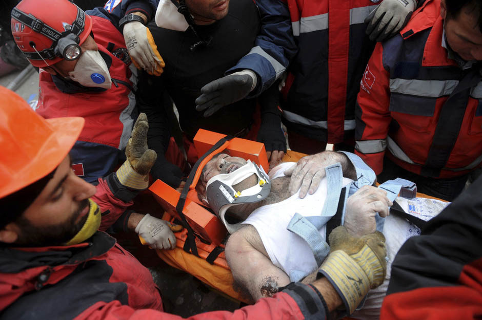 Rescue workers carry an earthquake survivor to an ambulance after he was found in a collapsed building in Van, eastern Turkey November 10, 2011. Rescue workers searched for survivors under the rubble of collapsed hotels in Van on Thursday after an earthquake which killed at least 13 people, less than three weeks after another killed 600 in the same area. [Credit : Evrim Aydin/AA/Reuters]
