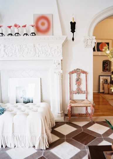 Here, a painted antique carved fireplace mantel becomes a chic decorative accent, paired with other finds from vintage to modern in an eclectic decor scheme (via belle maison)