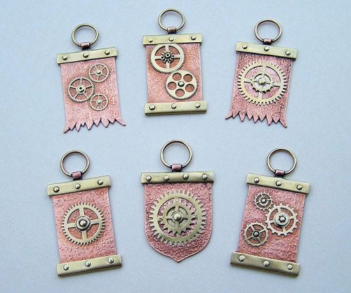 """Crest style steampunk trinkets riveted together from old gears and brass/copper plates etc. Heights are about 60 mm and those decorative patterns in the copper backgrouds are made with rolling mill."" ~(@)~ I'd want one for my key chain. ^^'"