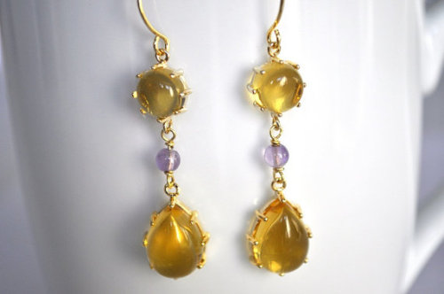 These earrings are made of 2 pieces of gold plated amber color framed glass; the round glass measures 8 mm and the drop like glass has a measurement of 15 mm long. between them, two small round purple amethysts (4 mm), all of them hanging from a gold plated earwire. Their total measurement is 5 cm long and will be delivered gift wrapped. On sale at www.mariacorcuera.com
