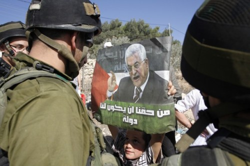 A Palestinian boy holds a picture of his leader Mahmoud Abbas with as slogan reading in Arabic, 'it is our right to have a state', as he stands in front of Israeli troops during a demonstration against Israel's apartheid -separation- wall in the West Bank village of Maasarah , near Bethlehem, on November 11, 2011. AP