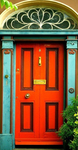 A wonderful bright and cheery front door painted orange, with turquoise accents, welcomes visitors to this home (via MAISON de BALLARD: When One Door Closes… Beautiful Doors From Around the World)
