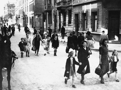 """German mothers walk their children to school through the streets of Aachen, Germany, on June 6, 1945, for registration at the first public school to be opened by the U.S. military government after the war."" (AP Photo/Peter J. Carroll)"
