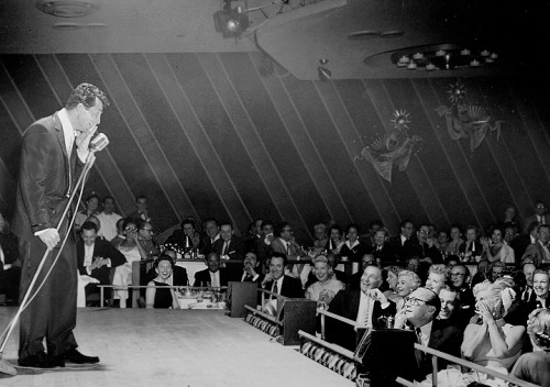 "Dean Martin performs at the Copa Room (1957). That's Lucille Ball, Desi Arnaz, Debbie Reynolds, & Jack Benny at the front table (click to enlarge) (via) ""In 1969, Orson Welles told me that he'd been backstage in his own Dean Martin Show dressing room when, before the taping, Dean knocked, then came in, drink in hand. 'Hey Orson,' he said, holding up his glass, 'you want one of these before we…?' Orson shook his head. 'No, no, Dean, I'm fine, thanks."" Martin looked shocked. ""You mean you're gonna go out there alone?!"" Welles roared with laughter when he told me the story. 'Alone!' he repeated loudly. 'Isn't that great!?' Orson went on, 'That's the best definition of addiction I've ever heard.'"" -Peter Bogdanovich (via)"