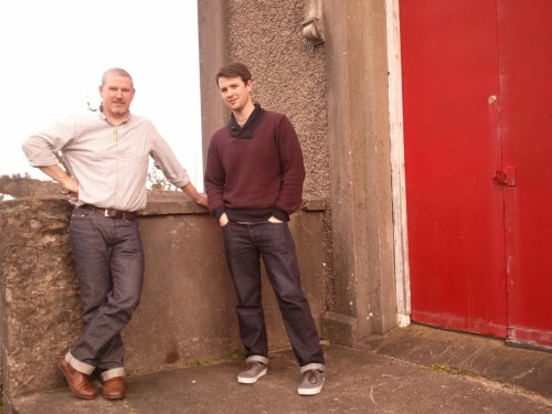 This is Sean and Kieran Molloy, two generations of a Donegal tweed weaving tradition that goes back many more. Kieran's grandfather (Sean's father) John Molloy started a tweed mill in Donegal, on the west coast of the northernmost part of the Republic of Ireland, fifty or so years ago. John was already a fourth- or fifth-generation weaver.  Over the years, John Molloy's business moved further and further away from weaving and towards knits, so Sean and Kieran started Molloy & Sons to make the traditional Donegal tweeds that the family had always woven. The factory sits in two barns, one new and one old, on land that has been used by Molloys for weaving for more than a century, a few steps from the house where both Sean and Kieran were reared. Above, Sean and Kieran are standing in front of their warehouse, a converted community theater. I spent a wonderful morning with the Molloys today, touring their modest two-man operation and learning about how tweed is made. Donegal tweed is a distinctive and remarkable form of the fabric, but it isn't protected by trade law as Harris Tweed is. This has meant that cheap Chinese and Italian knock-offs have pushed the industry in Donegal to the brink of disappearance. There are only two commercial tweed mills left in Donegal - the venerable (and sizable) Magee and these two fellas: Molloy & Sons. There's a recession bordering on depression in Ireland at the moment, and these two gifted craftsmen (and sharp businessmen) are fighting for a future for a textile tradition that their family has guarded for hundreds of years. I'll have a fuller writeup of my visit to Kieran and Sean's shop when I'm back in the States, but for now, check out these brave guys and their wonderful firm.