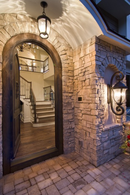 Wonderful front entrance with an arched door and lanterns (via Spur Road - Edina, MN - traditional - entry - minneapolis - by Schrader & Companies)