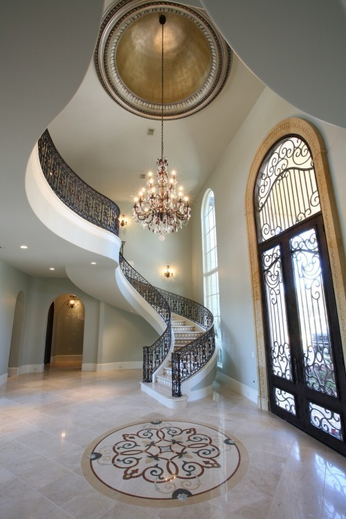 Jaw-dropping foyer with marble floors, an inlaid medallion, wrought iron railing on the stairs, crystal chandelier, and a gilded dome ceiling (via if I won the lottery / ugh, amazing)