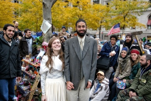 "Love blooms in Zuccotti  Park: Protesting  Occupy Wall Street lovebirds tie the knot  - NY Daily News Two lovebirds who met protesting Wall Street in Zuccotti Park tied the  knot Sunday morning at a humble ceremony in a small corner of the  ongoing demonstration. In front of about a dozen friends and onlookers, Emery Abdel-Latif, 24,  and Micha Balon, 19, held a traditional Muslim wedding on Trinity Place  and Liberty Street, perched on a small bench next to the park's famous  sculpture of a seated man with a briefcase. ""We have to be able to understand truly how unique this relationship  is,"" said Khalid Latif, the chaplain at New York University who married  the eager duo. ""You have been given a deep blessing today,"" he said. The two activists met in September when they were trying to find a  space in the crowded park to pray. They immediately hit it off. A month later, they both knew they wanted to spend the rest of their lives together - without delay. ""We met here and it's cheap. We don't have to pay anything,"" said the  giddy bride, dressed in a white skirt and blouse with a small cloak. ""I'm really glad God has granted me someone who cares about people in this world other than himself."" Balon, a Hunter College student from Staten Island studying human  rights and Middle East studies, said marrying in Zuccotti Park's ""sacred  space"" ensured their life together was starting on the right note. ""This is a good way not to make the marriage about ourselves,"" she  said. ""We are fighting for equality here. This is a great way to start  off our marriage."" Abdel-Latif, a prospective law student from West Chester County, Pa., said Balon changed his life. Read more: http://www.nydailynews.com/new-york/love-blooms-zuccotti-park-protesting-occupy-wall-street-lovebirds-tie-knot-article-1.976954#ixzz1ddeFQHqt"