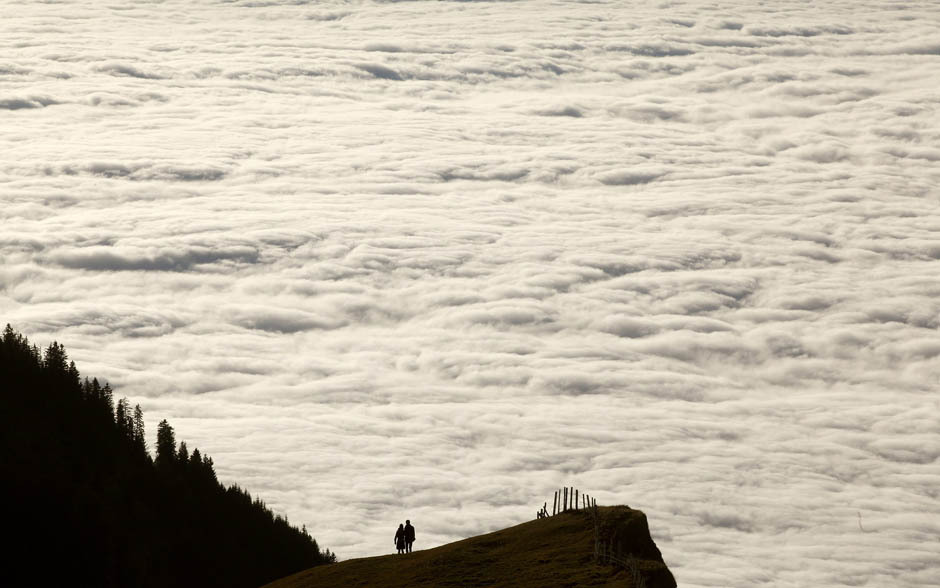 Photos of the day People look at the clouds during sunny autumn weather below the peak of Mount Rigi, 1,797m (5,896 ft) above sea level, near Lake Lucerne, Switzerland, November 13, 2011. (Photo: Arnd Wiegmann/Reuters)