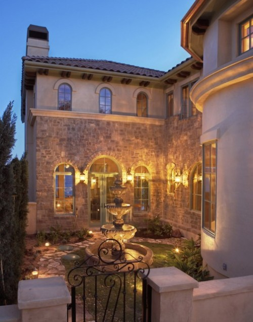A lighted courtyard with a fountain graces this Mediterranean style home (via Palmieri Residence - mediterranean - exterior - austin - by Vanguard Studio Inc.)