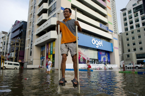 A man uses stilts to walk through floodwaters in Bangkok, on November 9, 2011. (Nicolas Asfouri/AFP/Getty Images) via @MarcusBurtBKK