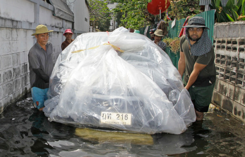 thai-flood-hacks:  Employees using an improvised float carry a car to a safer place as part of their shop's service at Bangkok Yai district in Bangkok, on November 9, 2011. (AP Photo/Sakchai Lalit) via @MarcusBurtBKK  zacskózott autó és egyéb elképesztő megoldások