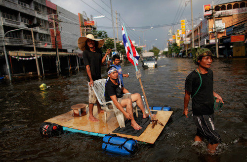A man pulls a makeshift raft carrying his friends and with a Thai national flag attached as they make their way through a newly flooded neighborhood in Bangkok's suburbs, on November 11, 2011 (Reuters/Damir Sagolj) via @MarcusBurtBKK