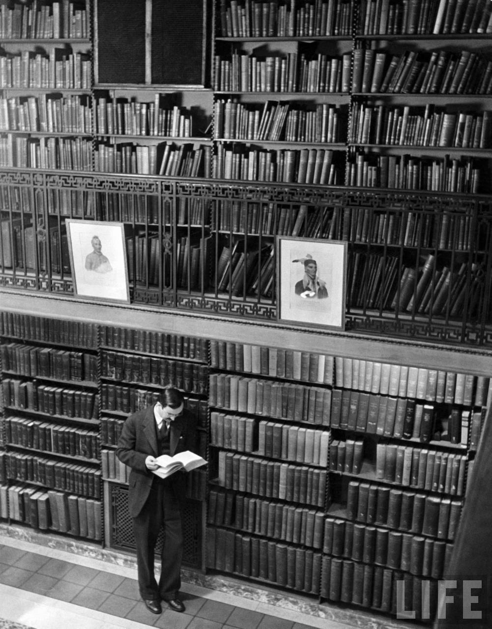 bookmania:  Author, Hoffman Reynolds Hays, reading book among shelves in American History Room in New York Public Library (1944) (via tatteredcover, bibliofila)