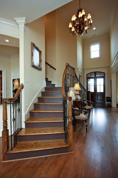 A beautiful double wooden staircase graces this front entrance hall (via entrances/foyers )