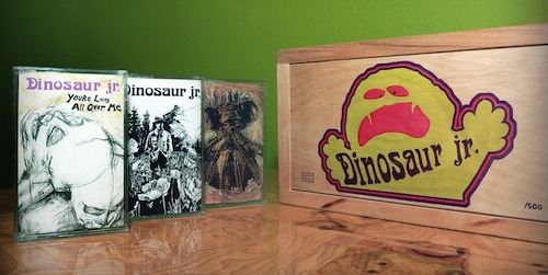 From the press release: Dinosaur Jr. have announced the reissue of their first three albums on cassette via Joyful Noise Recordings. Sold as a 3-album custom wooden box set – limited to just 500 copies – the Cassette Trilogy includes each album from the classic Dinosaur Jr. canon: 1985's Dinosaur, 1987's You're Living All Over Me, and 1988's Bug.