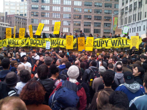 Hundreds of supporters of Occupy Wall Street vowed Tuesday to keep up their protests, convening  at a busy corner for a meeting to discuss their next move; the city, meanwhile, appeared headed for a legal showdown over its eviction of protesters from the group's encampment. A hearing was scheduled later on protesters' quest for an order to prohibit the city from banning tents, sleeping bags and campers from Zuccotti Park, a privately owned park that was cleared of protesters in a surprise early morning raid.  Photo: Occupy Wall Street supporters gather in a new spot after being cleared from Zuccotti Park in New York. Credit: Nathaniel Popper / Los Angeles Times