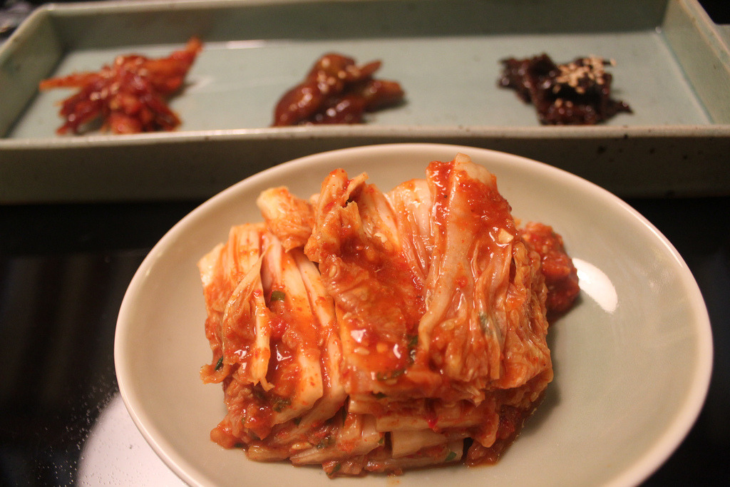 김치- Kimchi A traditional fermented Korean dish made of vegetables with varied seasonings. Kimchi may also refer to unfermented vegetable dishes. There are hundreds of varieties of kimchi made with a main vegetable ingredient such as napa cabbage, radish, green onions or cucumber. (wiki) by seoulkorea