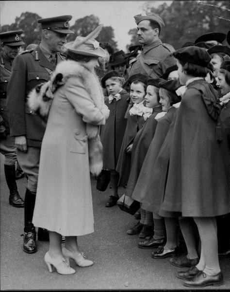 legrandcirque:  Queen Elizabeth chatting with a group of small girls during a ceremony in  which she presented the Canadian Saskatoon Light Infantry with company  colors, a gift of the people of Saskatoon to their boys serving  overseas. United Kingdom, October 1941.