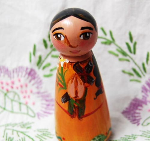 "Doll of Blessed Kateri Tekakwitha from Etsy seller St Anne's Pixies Kateri (or Catherine) Tekakwitha (1656-1680) was the daughter of a Mohawk chief and an Algonquian Catholic woman.  At the age of 4, she lost her parents and her brothers to a smallpox outbreak.  The outbreak left Kateri badly scarred with poor vision, which is why she was called ""Tekakwitha"" or ""she who bumps into things."" At the age of 20, Kateri was baptized as a Catholic.  She refused to marry, devoting her life to prayer and penitence.  This behavior provoked scorn from her tribe and Kateri soon left her home in New York State to join an established community of Native American Christians in Kahnawake, Quebec. At the mission, Kateri took a vow of chasity and became a sister.  On April 17, 1680, Kateri died at the age of 24.  Witnesses reported that within a few minutes of her death, the pock marks completely vanished from her face.  Several healing miracles were attributed to her after her death. Kateri was declared venerable by the Catholic Church in 1943 and was Beatified in 1980. The final step in her canonization is currently underway and Kateri could be named a saint soon.  Her feast day is July 14. Prayer circles are organized in the US and Canada to learn about and promote Kateri's saintly life.  Activist Sacheen Littlefeather coordinates San Fransisco's Kateri Prayer Circle.  A shrine in Fonda, NY is dedicated to her."