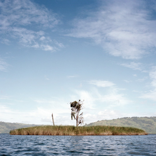Akampeine Island (aka Punishment Island) is a tiny one tree island in  Lake Bunyonyi. It was once a place where unmarried pregnant woman were  abandoned and left to die. Their only hope of rescue being, if a man too  poor to afford the price of a bride, would claim one of them to be his  wife. © Dillon Marsh