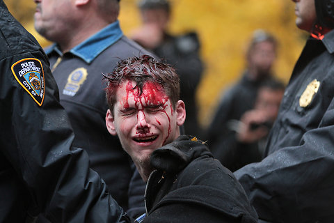 newsweek:  A bloodied protester at Zuccotti Park. More here, which alleges this punishment was for knocking off an officer's hat (including a shot of cops taking off his pants?!). [Photo by Chang W. Lee/The New York Times]