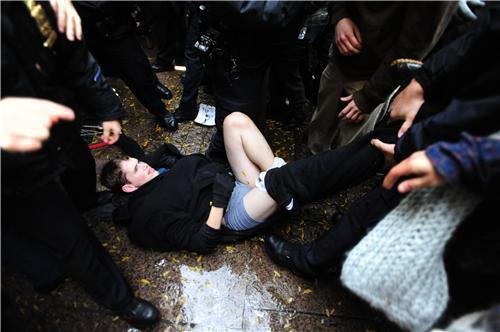 "youthiswasted:  Image of protester hit in the face with a police baton by NYPD officers.   Eyewitnesses then say what happened next was that the officers   repeatedly ""stomped"" on him when he was on the ground. Inexplicably,   NYPD officers stripped him of his pants and shoes and arrested him.   Ustream.tv/theother99 reports seeing bloodstains on the ground mixed   with the dirt and rain."