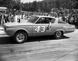 "Richard Petty pictured here with his 2nd Plymouth Barracuda (43/JR.) drag racer. The original had sported a bumper sticker that thumbed its nose at the NASCAR ban of Mopar's Hemi engine– ""NASCAR, If you can't outrun 'em, outlaw 'em."" ""Outlawed"" was also defiantly painted on the original 'Cuda's doors to further make the point. Read more…"