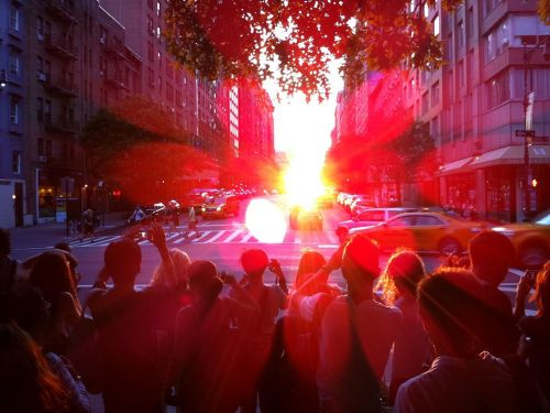 "nationalgeographicdaily:  Manhattan SolsticePhoto: Robinson McClellan Celebrating a ""Manhattan Solstice"" - when Manhattan's street grid lines up with the setting sun - in front of the American Museum of Natural History. On this day, New York City's vast edifice becomes ""Manhattanhenge,"" dedicated to sun worship!"