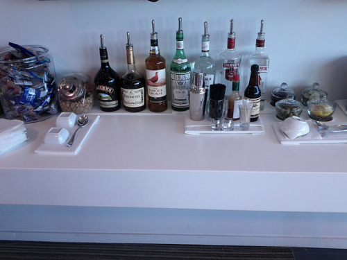 "My friend Toby posted this to Google+ and asked ""Airport club liquor selection. What can I make?""  Here's my answer: Let's start with the bar-setter's intent. Why are each of these here? The Bailey's, Hennessy cognac, and Famous Grouse Scotch are meant to be enjoyed alone (or the Bailey's with the hot chocolate that I bet is available off to the side). The vermouth is there to be combined with the Sminoff vodka or the Beefeater gin and one of the olives in on the right. The Bacardi is meant to be added to coke (also available offscreen). The vodka's other role would be with the tabasco and Worcheshire sauce in a Bloody Mary, or to be combined with tonic or soda and some of the lemon or lime wedges (the gin could do the last of these, as well).Assuming, those aren't to your liking, what else can we create? There are no bitters and no sweet liqueurs other than the Bailey's, which is going to make this tough. Let's do our best, though, and try to respect the context as well. Here's what I'd suggest:The Airport Aviation 1 3/4 oz Beefeater Gin 3/4 oz lemon juice (you're going to have to squeeze every one of those lemon wedges) 1/2 oz maraschino juice (behind the olives, to the left of the limes) Shake with ice, serve up and garnish with a maraschino cherryThis is an Aviation, but we've substituted maraschino juice for maraschino liqueur. We upped the gin and dropped the maraschino liqueur slightly to make up for the substitution."
