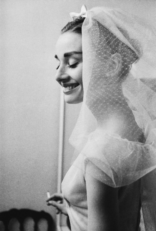 "rosettes:  1954:  Audrey Hepburn wears a wedding gown and veil in her role as Jo Stockton in Funny Face.  The photo was taken by David Seymour, who in 1947, helped found the first international cooperative photographic agency — Magnum.  The dance scene in which Audrey wears this costume was shot outdoors after weeks of torrential rain.  Audrey had nine pairs of white satin dancing shoes that were made in Paris that she had to continuously swap out as each became muddied beyond use.  ""Here I've been waiting for twenty years to dance with Fred Astaire,"" Audrey quipped, ""and what do I get?  Mud in my eye!"""