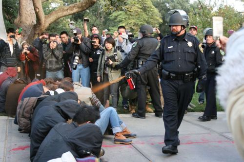 jtotheizzoe:  motherjones:  UC Davis police officer pepper sprays sitting students because, well, just because. Think that's %$#ing horrible? The video's worse. Via John Aravosis at AmericaBlog:  I'm sorry, this has gone too far. This has happened in police department  after police department, and it has gone too far. Our police look like  the goons in Russia and China. Please watch this video and send it to  everyone you know. This has gone too far.   Too important not to speak up. This isn't about your views or understanding (or lack, or misconception) of the Occupy movement anymore, it's about rights and abuse thereof. Equally shocking photoset here and video here.  Simply appalling. Who else does it bother that the American government and authorities call attacks on protesters to be despicable, but fully condone it here? Hypocrisy much?
