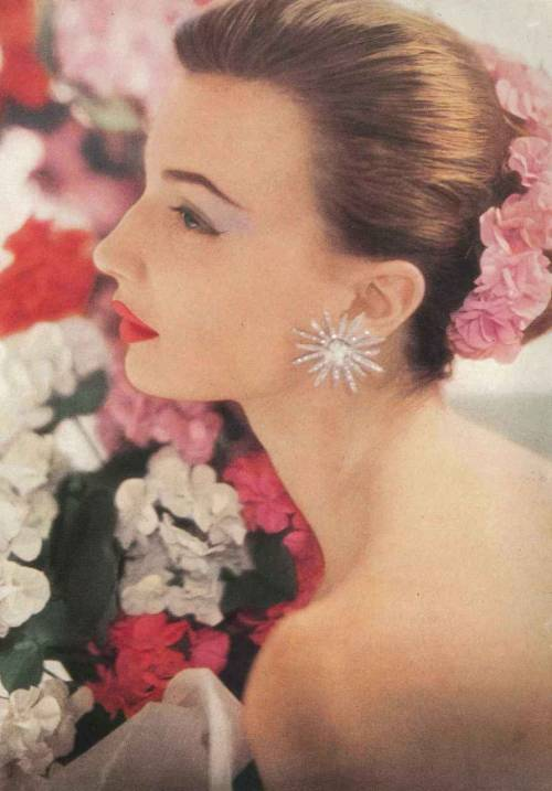 June Vogue 1952 Photo by Roger Prigent  Maria Reachi, daughter of silent film actress Agnes Ayres, wears her hair swept back in a flowered-garlanded chignon. Her lipstick is 'Pink Geranium' by Charles of the Ritz.