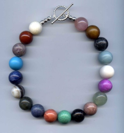 The19 individual extra-large round semiprecious stone beads used making this neck ornament look like it's made of big gumballs (no 2 the same).  This choker with its .999 sterling silver toggle plus all the different stones represented makes this a necklace for any occassion.  Picture wearing this necklace dressed down with a nice crisp white linen shirt and jeans or dress it up and wear it with your little black dress and lots of silver bangles then add some silver chandelier earrings for a late night romantic restaurant rendezvous! © 2011 George13Walters