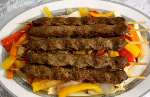 Beef Kebabs  Since it's no longer warm enough for summer BBQ's, I've decided to turn my oven into a grill. Bring the BBQ indoors and you'll get a taste of Summer year round. These delicious beef kebabs are a great appetizer or meal…Perfect for entertaining guests. Now the only thing that's missing is a pool and some sunshine!  Dish Type: Meat- Meal/ Appetizer Prep Time: 5 minutes Total Time: 1 hour 20 minutes Ingredients 5 spiced beef kebabs 1 yellow onion 1 yellow pepper 1 red pepper 1 orange pepper 1 Tbsp olive oil 1 tsp minced garlic  dash of salt dash of pepper Instructions Preheat oven to 350 degrees. Slice peppers and onions into long thin strips. Combine with olive oil, garlic, salt and pepper and transfer to a cast iron skillet or baking tin. Bake for 15 minutes, then remove from oven. Turn peppers and onions for even cooking and add beef kebabs on top. Cook for 30 minutes then turn kebabs for an additional 30 minutes. Serve with a whole wheat pita and hummus (optional). Enjoy! Serves: 5 Nutrition Info (per kebab and veggie portion): 176 cals, 7g fat, 8g carb, 3g fiber, 8g protein, 570mg sodium