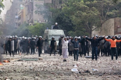 aljazeera:  Men form a human chain in front of police to prevent protesters from throwing stones at them on Sunday. [Retuers]