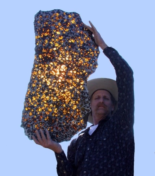 cwnl:  Piece Of The Galaxy In Your Hands That's a fukang awesome meteorite! Photo of a man holding a rare meteorite known as the Fukang Pallasite with sun rays passing through its crystals. 'The Fukang meteorite was found in the mountains near Fukang, China in 2000. Pallasites are a type of stony–iron meteorite with beautiful olivine crystals.'